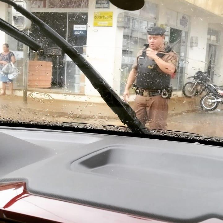 Mesmo com a forte chuva o policial militar continuou o serviço no controle do trânsito em Manhuaçu