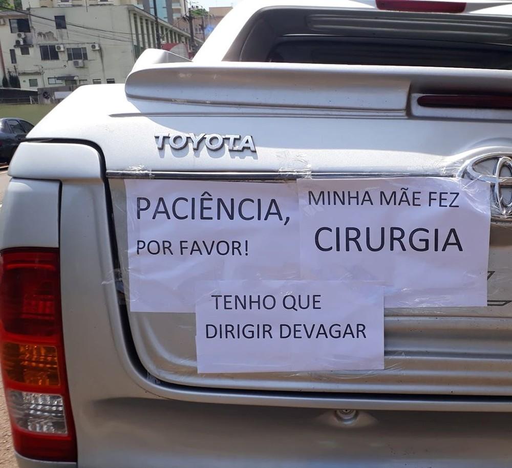 """Com três cartazes colocados na traseira da caminhonete, Audmara fez o apelo: """"Paciência, por favor! Minhã mãe fez cirurgia. Tenho que dirigir devagar"""